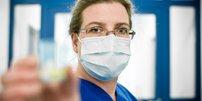 Frau mit Mundschutz im Krankenhaus hält Medizin in der Hand