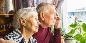 Älteres Paar schaut aus dem Fenster