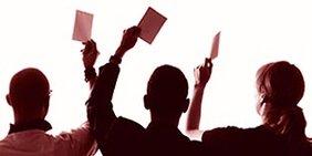 3 Menschen heben ihre Stimmkarte