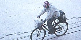 Frau auf Fahrrad im Schnee, fahrrend