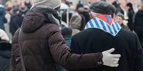 Junge Frau legt im ehemaligen KZ Auschwitz bei einer Gedenkfeier ihren Arm um einen Auschwitz-Überlebenden