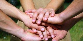 Übereinander gelegte Hände mehrerer Personen (Symbolbild: Team)