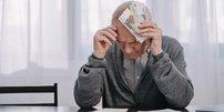 Rentner sitzt mit Geldscheinen am Kopf an Rechnungen