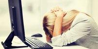 Erschöpfte blonde Frau legt Kopf auf den Schreibtisch