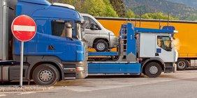 """Mehrere parkende Lkw auf einem Rastplatz, im Vordergrund ein """"Einfahrt verboten""""-Schild"""