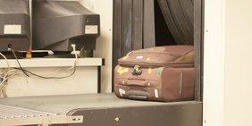 Reisekoffer wird am Flughafen durch Röntgengerät befördert