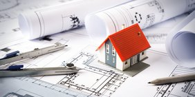 Kleines Modell-Haus mit Plänen, Stift und Zirkel