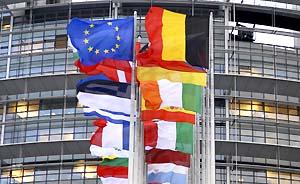 Eine EU-Flagge und Flaggen der EU-Mitgliedsstaaten vor dem Gebäude des Europäischen Parlaments