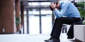Mann mit Busineshemd mit über den Kopf geschlagenen Händen und Kopf nach unten hängend